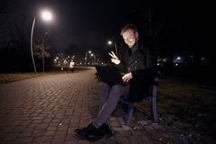 Dark night, one young man, 20-29 years, sitting on bench alone, using his laptop in public park in Autumn. gesturing Hello or Hi, stock images