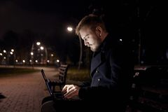 Dark night, one young man, 20-29 years, sitting on bench alone, using his laptop typing on keyboard, in public park in Autumn stock photo