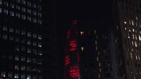 Office tower skyscraper lit up at night. Dark night shot of tall office tower or skyscraper in big city lit up with red colors. Light performance or art stock footage