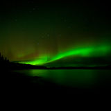 Dark night sky Northern Lights illuminated Stock Photography