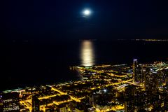 Night city lights with moonlight on the lake royalty free stock image