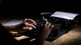 Dark night, a man on a typewriter writes a book. Dark night in a spacious study, a man sits at a table and writes a book on a typewriter stock footage
