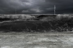 Dark ocean in storm with lightening and waves. Flooding concrete ground Stock Photography