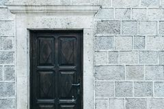 Dark old door  on an  gray stone wall. Place for text Stock Photos