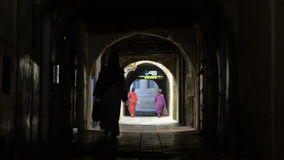 Dark old tunnel in ancient arabic city Essaouira, Morocco. Dark old street of Essaouira in Morocco and two women in national dress walking away from the camera stock footage