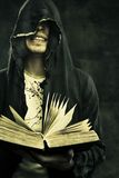 Dark omen. Portrait of sinister prophet in hood holding book Royalty Free Stock Images