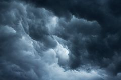 DARK STORM CLOUDS. Dark ominous cloud situated low in the sky with patch of light stock photo