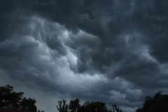 STORM CLOUDS ABOVE TREES. Dark ominous cloud situated low in the sky with patch of light royalty free stock photo