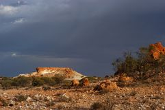 Major Thunderstorm approaching breakaways. Dark ominous clouds forming for a thunderstorm in the outback of Australia. Sunlit breakaways underneath a terrible royalty free stock photos