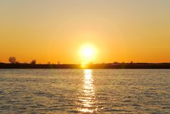 Golden yellow sunset over the river. Dark orange sunset over the river. Beautiful evening landscape on the Volga river in the spring Stock Images