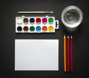On a dark paint background brush pencils colored glasses of water horizontal top view flat lay knolling. N Stock Photo