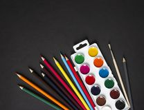 On a dark paint background brush pencils colored horizontal top view flat lay knolling Stock Photos