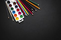 On a dark paint background brush pencils colored horizontal top view flat lay knolling. N Stock Image