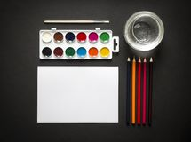 On a dark paint background brush pencils colored water sheet paper horisontal top view flat lay knolling Stock Images