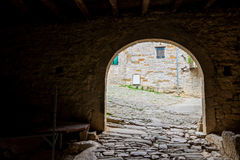 Dark passageway with arch to the light Stock Photography