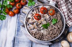 Dark pasta with vegetables. In white sauce on wooden background. Selective focus Stock Photos