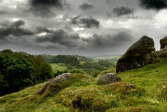 Dark Patchy Clouds over the Peaks. Dark patchy clouds gather over the Peak District National Park, UK. Layers of rolling hills with trees, rock and grass growing Stock Photography