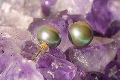 Dark pearl earrings on ametyst background. Pair of dark earrings on ametyst background Royalty Free Stock Photos