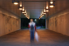 Dark pedestrian subway. Floodlit pedestrian subway at dusk, single young lady walking through (motion blurred royalty free stock photo