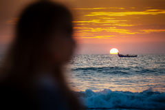 Dark person silhouette at sun disk rising from behind azure sea. Dark person's silhouette against large bright sun disk rising from behind azure sea in golden Stock Image
