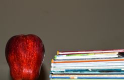 A dark photo of an apple beside a stack of children`s book for education. A red, shiny apple beside a stack of children`s book for education for school, home or Stock Image