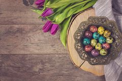 Dark photo of Easter quail eggs in an ancient metal bowl. Beautiful spring flowers - purple tulips on a wooden background. Floral stock image