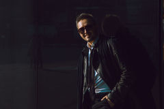 Dark photo of fun business man in leather suit and sunglasses ne Stock Image