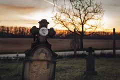Dark photo of old and abandoned cross grave stone on European cemetery with tree and forest on background on sunset. Creepy and. Illuminated tombstones on stock photos