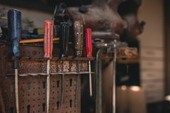 Dark photo of screw drivers hanging on the tool panel in old shed on sunset. Close up photo of colorful working tools on the wall stock photography