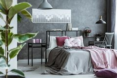 Dark pink bedroom interior. In the background bed with white knot pillow between nightstands with candles and clock in dark bedroom interior with pink blanket Royalty Free Stock Photography