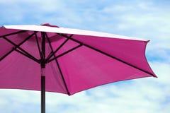 Dark pink parasol. On blue coudy sky stock photos