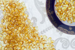 Dark plate with yellow amber stones. Lie on a light fabric Stock Images