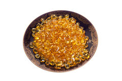 Dark plate with yellow amber stones. On a white background Royalty Free Stock Photography