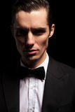 Dark portrait of classy man in tuxedo with bowtie. Close portrait of classy man in tuxedo with bowtie posing in dark studio background looking at the camera royalty free stock images