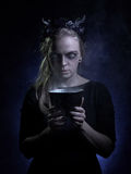 Dark portrait of evil witch in smoke.  stock photography