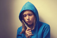 Dark portrait of a junk teen girl with syringe Royalty Free Stock Photography