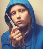 Dark portrait of a junk teen girl with syringe Stock Photography