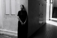 Dark portrait of sad Asian woman in black clothes. At the old building royalty free stock image