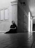 Dark portrait of sad Asian woman in black clothes. At the old building stock photo