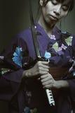 Dark portrait of samurai woman. Dark portrait of a dangerous samurai woman . Studio shot stock photo