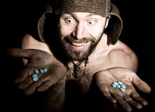 Dark portrait of scary evil sinister bearded man with smirk, holds in palm of a bunch of pills. strange Russian man with Stock Image