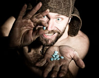 Dark portrait of scary evil sinister bearded man with smirk, holds in palm of a bunch of pills. strange Russian man with Royalty Free Stock Photo
