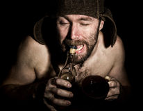 Dark portrait of scary evil sinister bearded man with smirk, he opens a bottle of brandy his teeth . strange Russian man Stock Photography