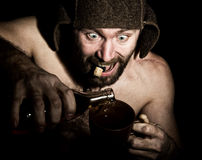 Dark portrait of scary evil sinister bearded man with smirk, he pours brandy in a cup of coffee. strange Russian man Royalty Free Stock Image