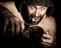 Dark portrait of scary evil sinister bearded man with smirk, he pours brandy in a cup of coffee. strange Russian man Stock Photos
