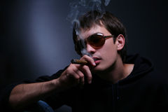 Dark portrait of a smoking man in sunglasses Royalty Free Stock Photography