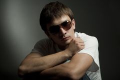 Dark portrait of a young man in sunglasses Royalty Free Stock Image
