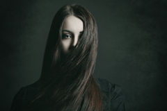 Dark portrait of a young woman. With long hair . Halloween and horror concept