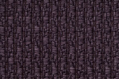 Dark purple knitted woolen background with a pattern of soft, fleecy cloth. Texture of textile closeup. Royalty Free Stock Image