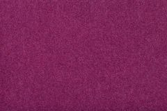 Dark purple matt suede fabric closeup. Velvet texture of felt stock photography